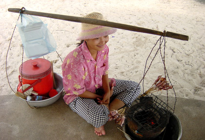 woman selling grilled squid at a beach in Sihanoukville, Cambodia