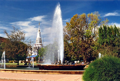 fountain on a park near the city center with the Wat Phnom in the left background