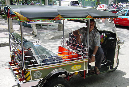a tuk-tuk or 3-wheeled taxi parked on a Bangkok street