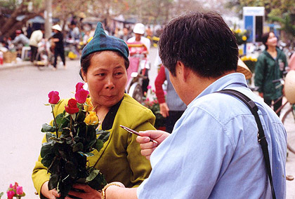 tourist buying flowers at a roadside stall in Hanoi, Vietnam