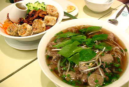 a bowl of seafood pho with a bowl of grilled chicken and fried spring rolls