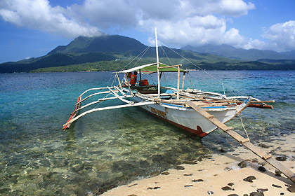 outrigger boat on Dalutan Island with the main island of Biliran in the background