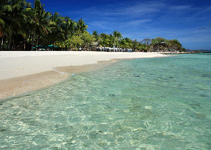 Malcapuya Island's white sand southern beach