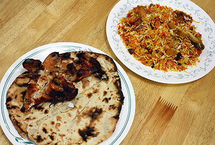 a plate of chicken tikka and naan bread in the foreground and a plate of chicken biryani in the background