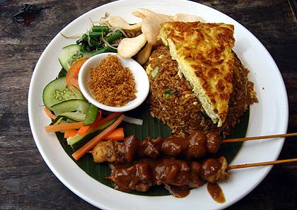 a plate of nasi goreng, fried egg, kerupuk and sate ayam